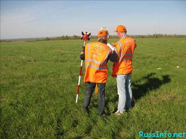 работники измеряют землю