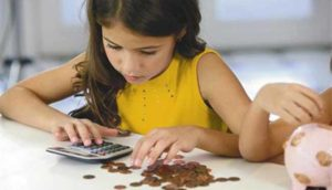 девочка считает на калькуляторе мелочь