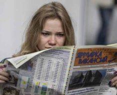 девушка просматривает вакансии по газете