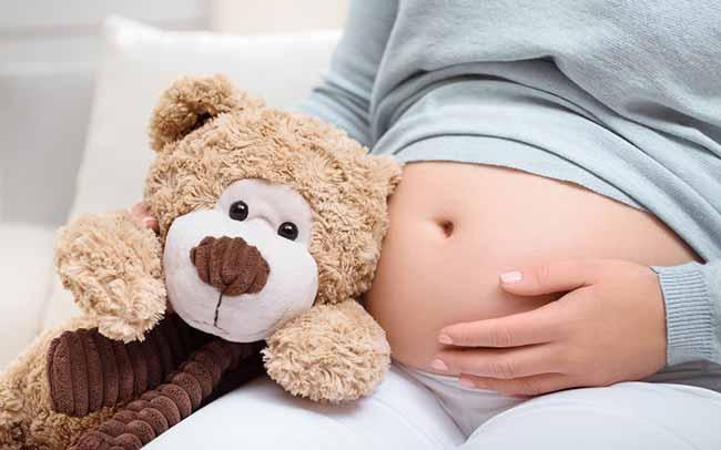 Беременная девушка с игрушкой
