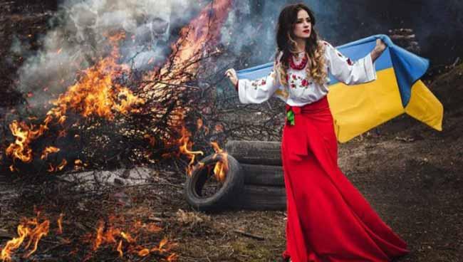 Девушка с флагом Украины на фоне огня