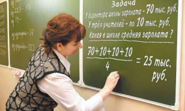 Учитель пишет мелом на доске