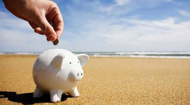 Свинья копилка на песочном пляже