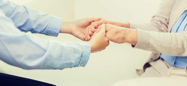Руки пенсионера в пуках социального работника